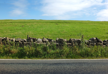view of an empty country road with an overgrown dry stone wall with a fence separating it from a bright green hilly meadow with blue summer sky and white clouds
