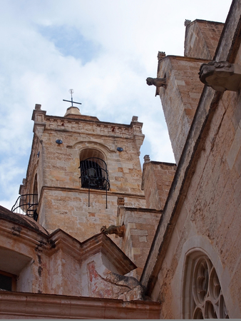 A close up view of the bell tower and gargoyles of the Santa Maria Cathedral in La Ciutadella in Menorca against a blue cloudy sky Stock Photo