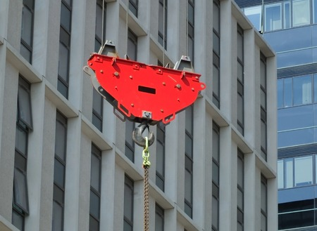 a bright red crane hook and pulley lifting a suspended metal chain on a construction site with urban modern buildings in the background