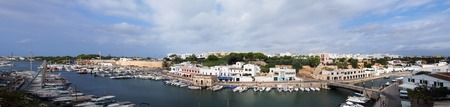 A wide panorama view of the town of ciutadella in menorca showing boats moored along the canal and surrounding buildings in bright summer sunlight