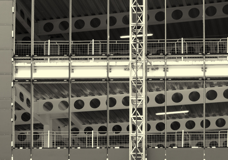 monochrome image of a large construction site with steel framework and girders with fences and building hoist