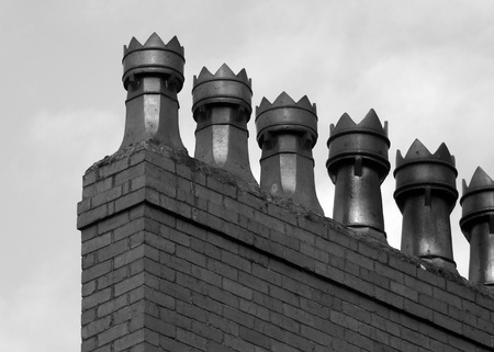 monochrome image of a row old fashioned chimney pots on a brick built house