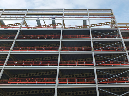 vertical upwards view of a large building development under construction with steel framework and girders supporting the metal floors with blue sky and clouds Stock Photo