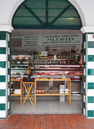 A traditional meat shop in the old Ciutadella town market with a sign advertising quality meat and products in spanish
