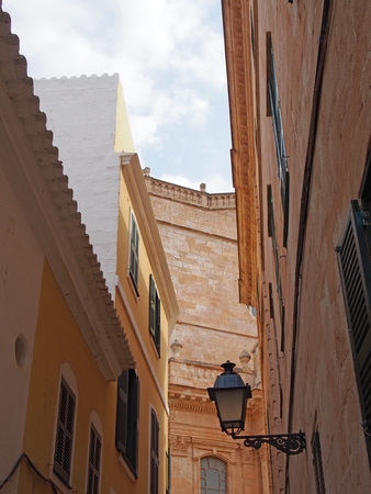 picturesque street view of ciutadella looking upwards at the facade of the cathedral with old shuttered windows and balconies against a blue summer sky