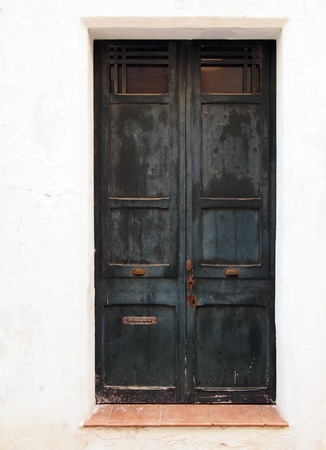 old wooden black double doors with chipped flaking faded peeling paint and rusty handles lock and letterbox in a white painted wall and tile doorstep
