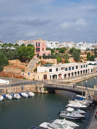 view of the harbour in ciutadella menorca with moored boats and surrounding buildings in blue summer sunlight Stock Photo