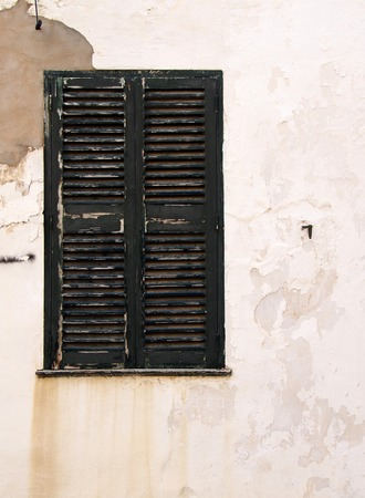 picturesque ancient close wooden shutters painted dark green on the whitewashed flaking peeling distressed old house wall