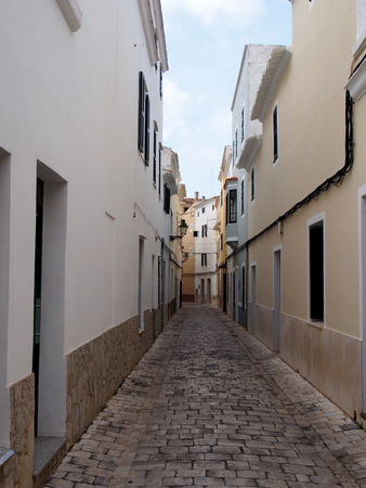 a typical narrow cobbled street of traditional painted houses in ciutadella menorca Stock Photo
