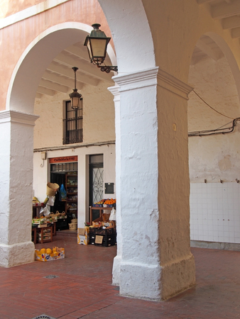 Ciutadella, Menorca, Spain - October 1 2018: the traditional old market square in ciutadella menorca with a vegetable shop behind the pillars and arches Editorial