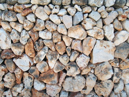 Old irregular loose stone wall made of large textured brown and white limestone rocks with old twigs interwoven in the surface