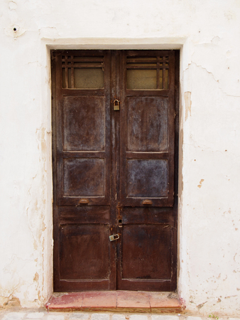 old wooden brown double doors with chipped flaking faded peeling paint and rusty handles padlocked closed in a white painted wall and tile doorstep