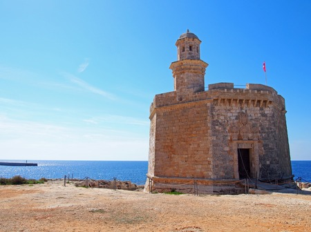 The Sant Nicolau Castle in ciutadella menorca on the cliffs with blue summer sea and blue sky