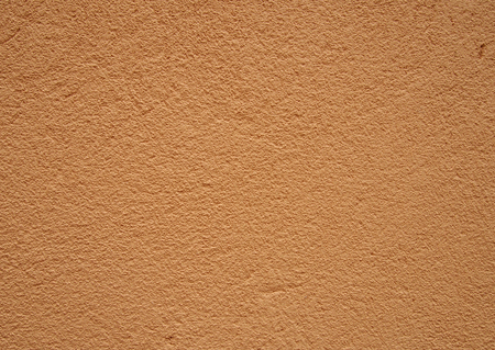rough textured light beige orange textured gritty rough wall surface background Stock Photo