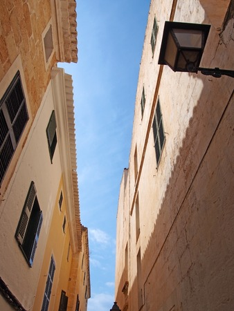 upwards view of a typical old narrow street in ciutadella menorca with old stone buildings with shutters and street light against a bright blue sky in summer sunlight and shadow