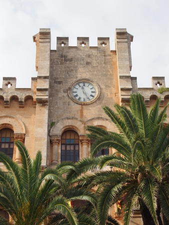view of the historic town hall in ciutadella menorca surrounded by palm trees and blue sunlit summer sky