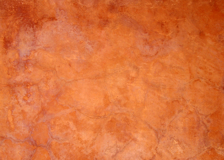 old bright orange brown painted faded stained cracked rough plaster wall background Stockfoto