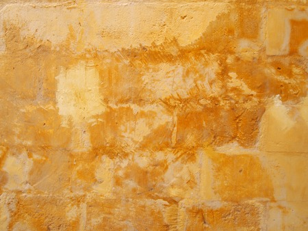 an old distressed patched yellow stone wall painted in different shades of faded stained bright yellow paint
