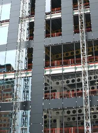 close up view of a modern construction site with hoists running up the tall building with steel girders with black panels and windows being installed