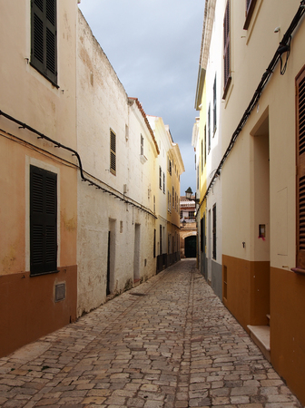 a long straight cobbled picturesque empty narrow street of old houses in cuitadella menorca Stock Photo