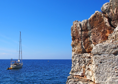 a yacht on a bright calm Mediterranean sea next to beautiful rugged cliffs on the minorcan coastline in bright blue summer sunshine