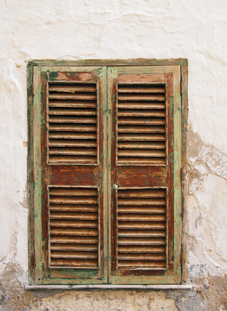 ancient closed green painted brown window shutters in a white wall with cracked cement and plaster