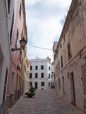 a picturesque quiet empty typical street in ciutadella menorca with old traditional houses and a street lamp with blue cloudy sky 스톡 콘텐츠