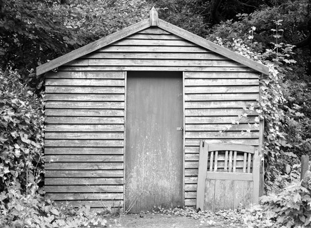 a monochrome image of an old wooden shed with a discarded gate surrounded by woodland trees and vegetation
