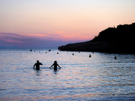 A sunset bay in menorca with purple and orange sky with an unidentifiable couple in silhouette in the dark blue calm evening sea
