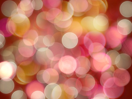 Bright coloured yellow and pink round blurred lights on a glowing red background abstract