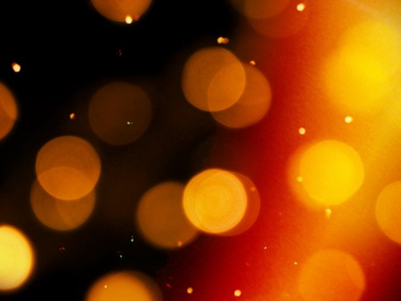 golden orange glow on a black background with round blurred lights and bright yellow sparkles