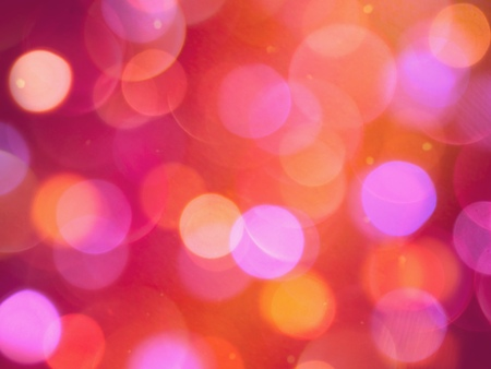 Bright coloured round blurred lights on a glowing warm red background