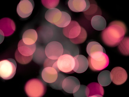 Pink glowing blurred round lights on a black background