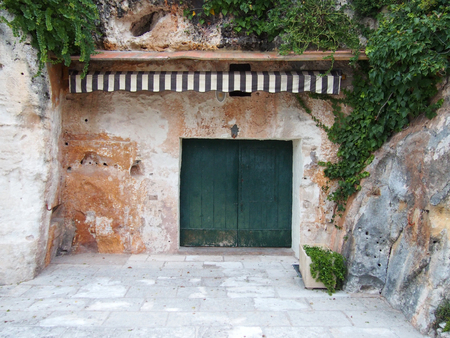 A stone shelter carved out of a cliff with green vegetation wooden doors and a striped awning