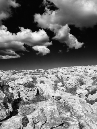 monochome surreal image of a harsh rocky nanscape in bright light with dark contrasting sky and white clouds Stock Photo