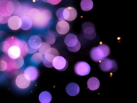 sparkling purple round bright blurred lights on a black background