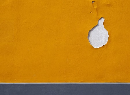 bright yellow textured paint on an external wall with cracks and hole flaking away and grey horizontal stripe at the bottom