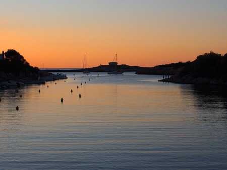 The cala santandria in ciutadella at twilight with a glowing orange evening sky reflected in dark blue calm water of the bay with boats and coast in silhouette