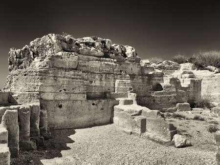 Monochrome image of old ruined quarry workings carved out in geometric shapes