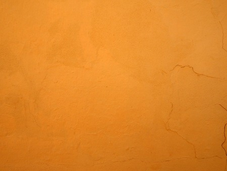 a bright rough textured orange paint with cracks on a plastered concrete wall Stock Photo