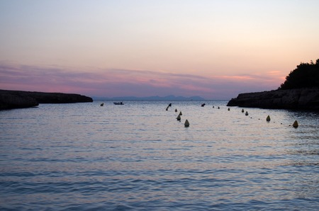 The bay in the cala santandria in ciutadella at twilight with a glowing purple and pink evening sky reflected in dark blue calm water with small boat and land in silhouette