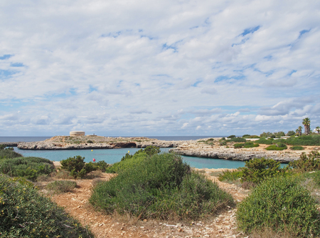 a stone path with a view of the coastline and the old british era Torre des Castellar at the edge of the bay in cala santandria near cuitadella with bright blue sea and summer clouds Stock Photo