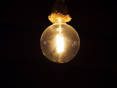 An old vintage dusty edison light bulb hanging on a rope fixture glowing against a black background