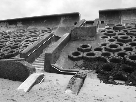monochrome image of the seawall south of blackpool constructed of concrete honeycomb type structures with steps leading to the beach covered in tidal seaweed and dramatic grey sky