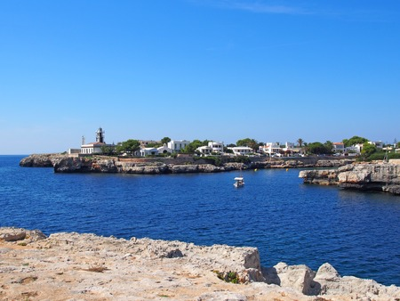 a view of Cala Santandria with lighthouse and boat in a bright summers day in Menorca Spain Stock Photo