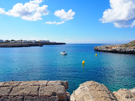 view across the bay in cala santandria menorca with old military ruins looking out on to bright blue sea Stock Photo