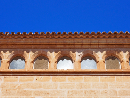close up of the roof line of an old stone spanish building with curved tiles and ornate windows with a bright blue sunlit sky