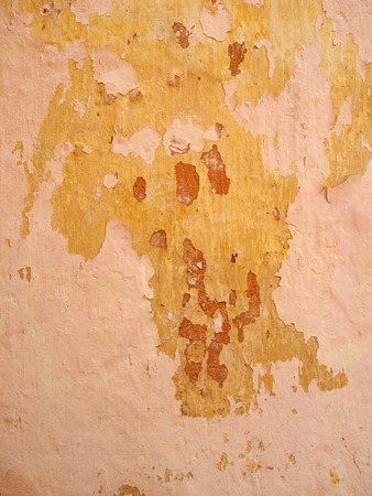 an old rough painted wall with peeling layers of pink red and yellow paint