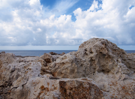 rugged rocks against a deep blue sea with bright sky with white clouds in menorca spain travel or vacation background