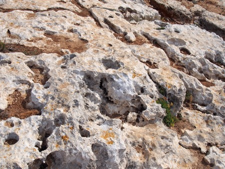 rough grey eroded limestone ground on a beach with scattered sand Stock Photo